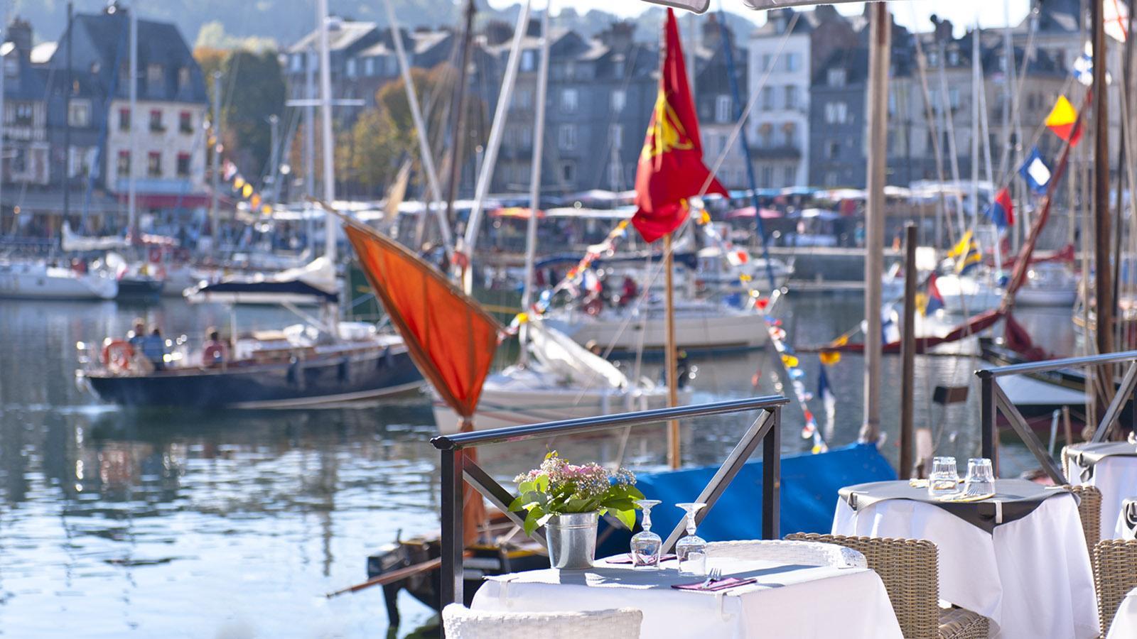 Schlemmen direkt in der Wasserkante: In Honfleur säumen Restaurants dicht an dicht die Kais des Vieux-Port. Foto: Hilke Maunder