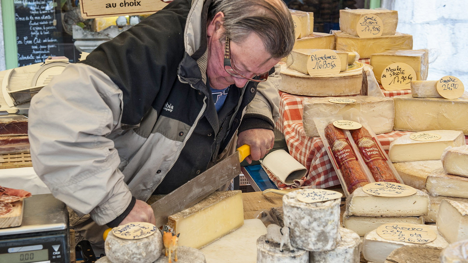 Sonntagsmarkt von Annecy. Käseschneiden kostet Kraft! Foto: Hilke Maunder