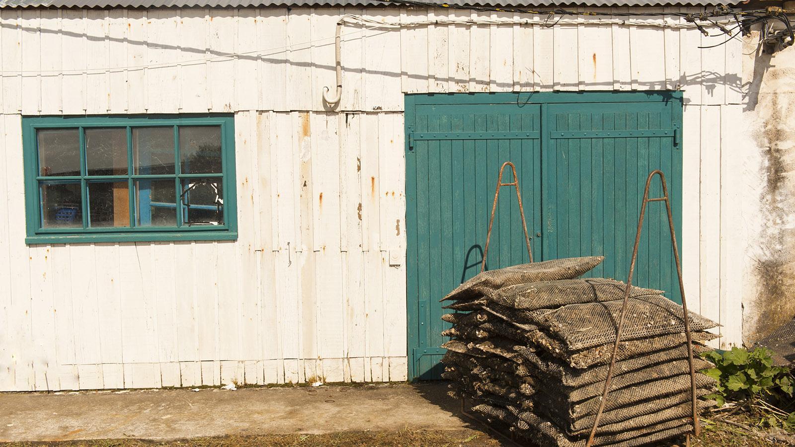 Île d'Oléron: Austernsäcke lagern vor den Hütten am Hafen von Saint-Trojan-les-Bains. Foto. Hilke Maunder