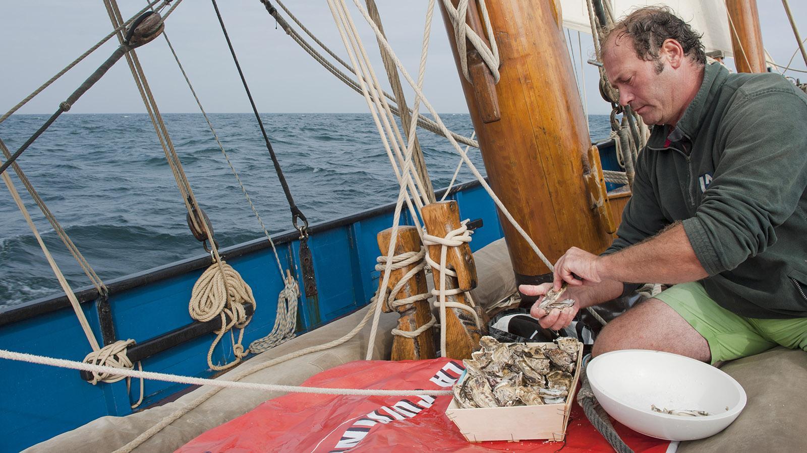 "Cuisine Corsaire: Jerôme Foyer öffnet Austern an Bord der Bisquine ""La Cancalaise"". Foto: Hilke Maunder"