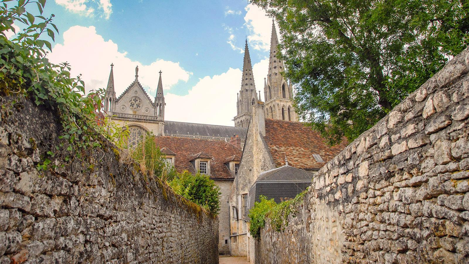 Eine schmale Gasse, umgeben von hohen Feldsteinmauern, führt zur Kathedrale von Sées. Foto: Hilke Maunder
