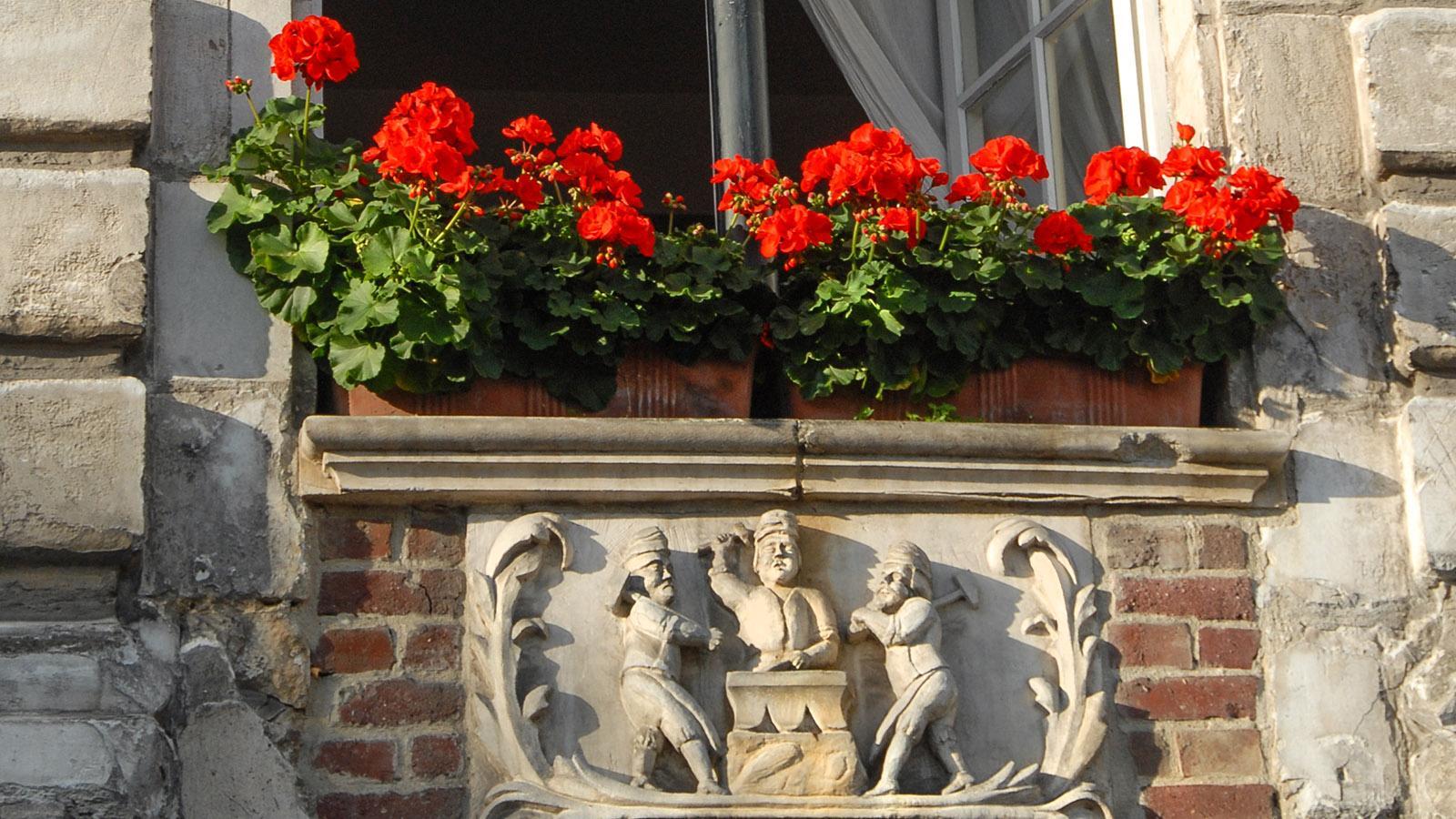 Arras:. Unter den Fensterbänken schmücken Steinschnitzereien die Fenster der flämischen Bürgerhäuser an der Grande Place. Foto: Hilke Maunder
