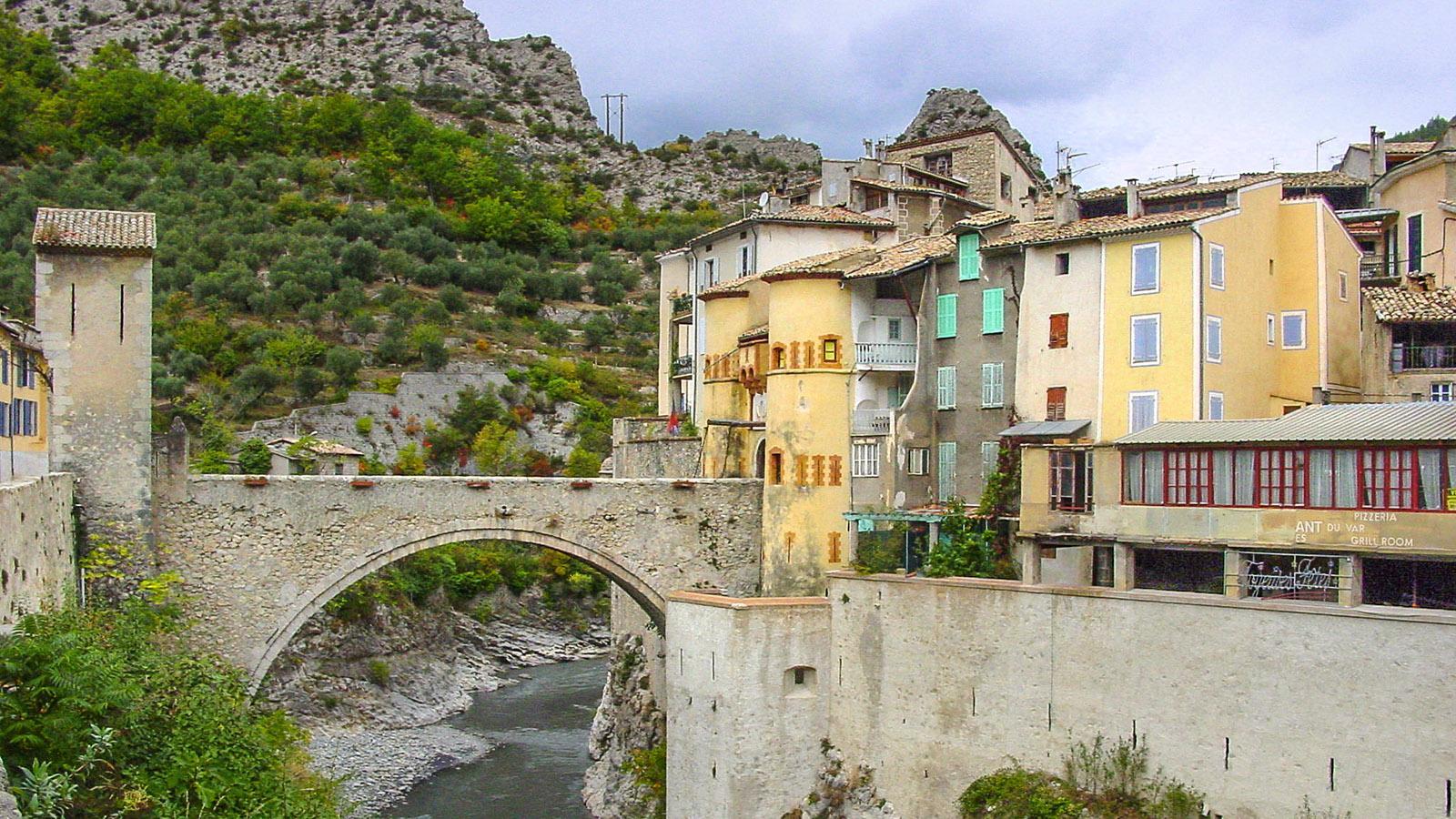 Entrevaux: Eine Brücke überspannt den Var und führt durch ein mächtiges Stadttor samt Zugbrücke in den mittelalterlichen Ortskern. Foto: Hilke Maunder