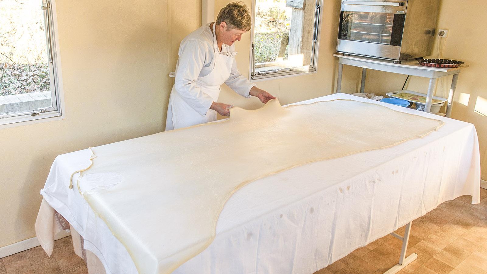 Isabelle Ducourneau zieht den Teig vorsichtig hauchdünn auf dem Küchentisch aus. Foto: Hilke Maunder