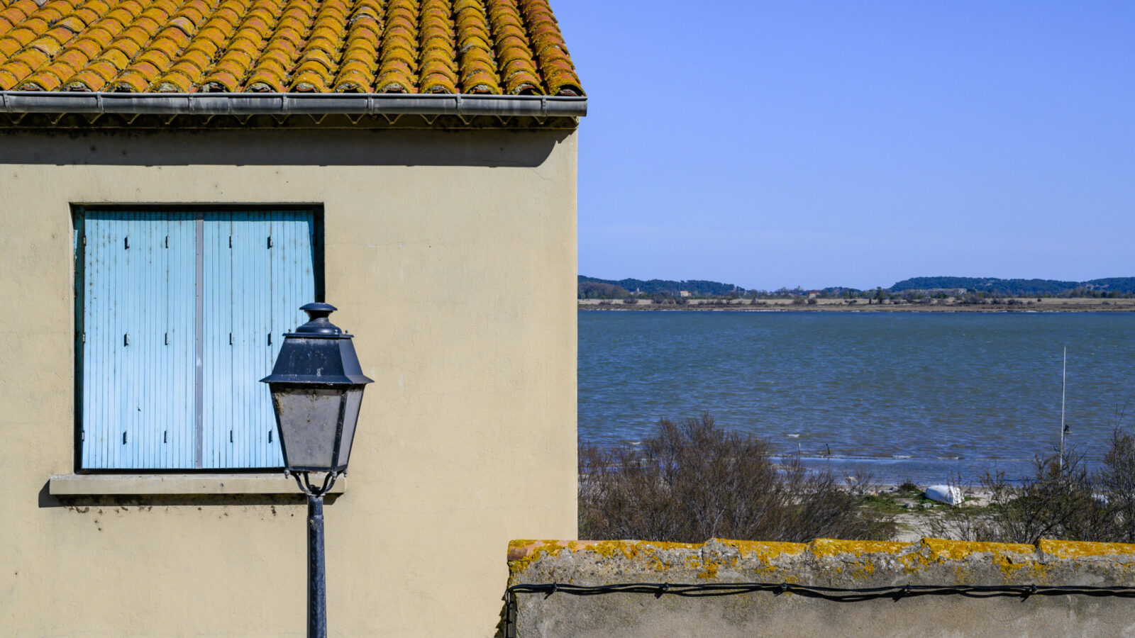 Immer wieder blitzt zwischen den Fassaden das Blau des Étang de Bages auf, Foto: Hilke Maunder