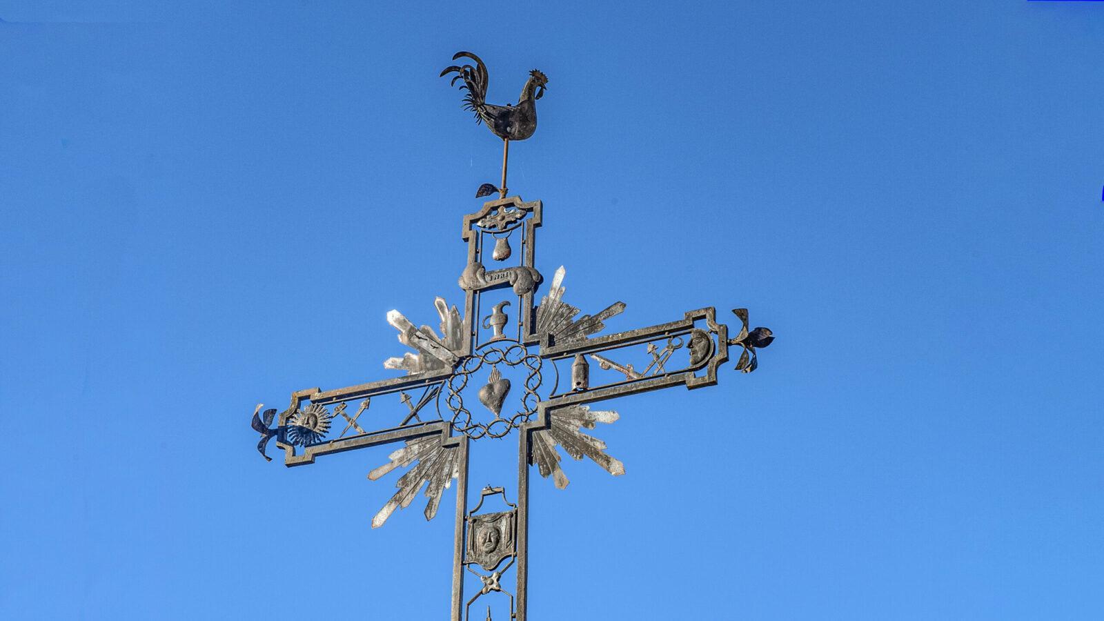 Die Wetterfahne der Pfarrkirche erhebt sich auf dem Kirchvorplatz. Foto: Hilke Maunder