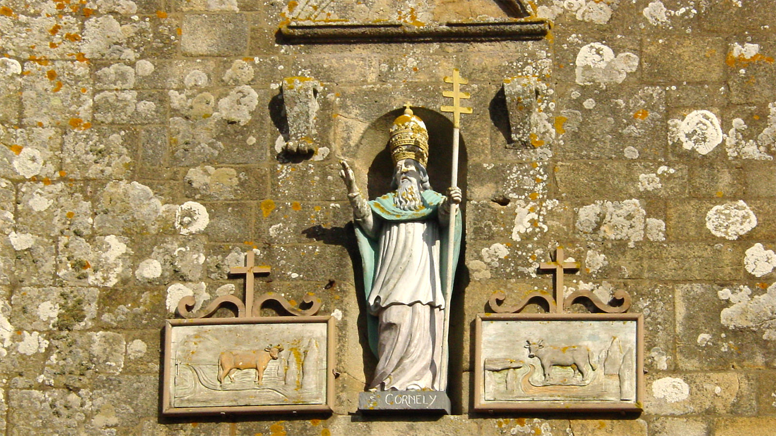 Bretagne/Carnac/Kirche St-Cornély: Die Kirche dem heiligen Cornelius geweiht, dem Schutzpatron des Hornviehs. Zwei Ochsen flankieren die Statue des Heiligen über dem Haupteingang der Kirche. Foto: Hilke Maunder