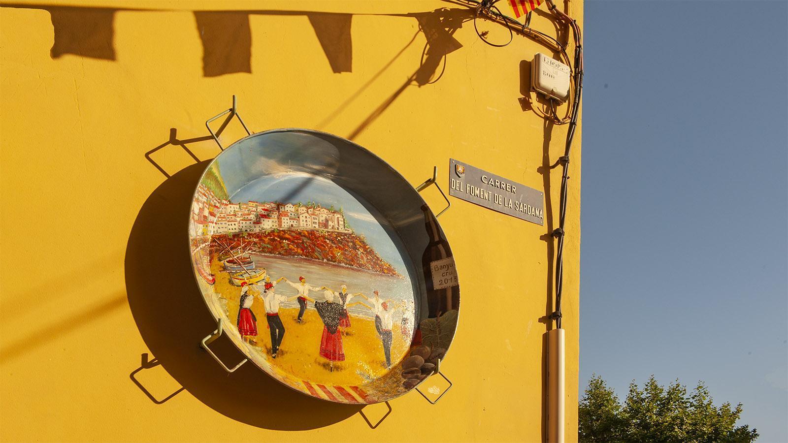 """Banyuls: Diese Straße erinnert mit ihrem Namen und einer bemalten Paella-Pfanne an den ktalanischen Reigentanz """"Sardane"""". Foto: Hilke Maunder"""