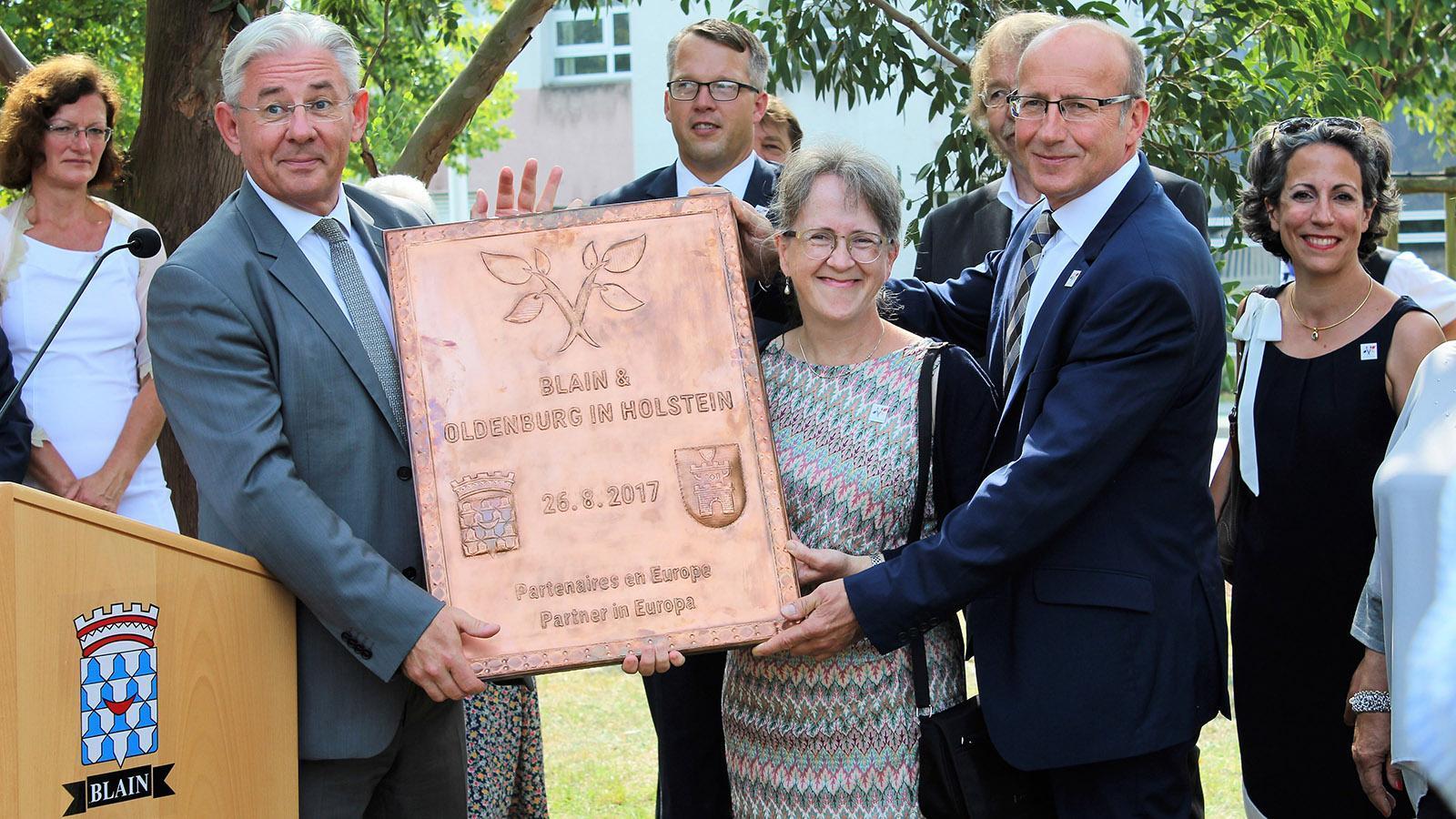 Oldenburgs Bürgermeister Martin Voigt (.) und Blains Bürgermeister Jean-Michel Buf (4.v.l.) mit dem Oldenburger Geschenk - der Kupferplakette. Foto: Stadt Oldenburg in Holstein.