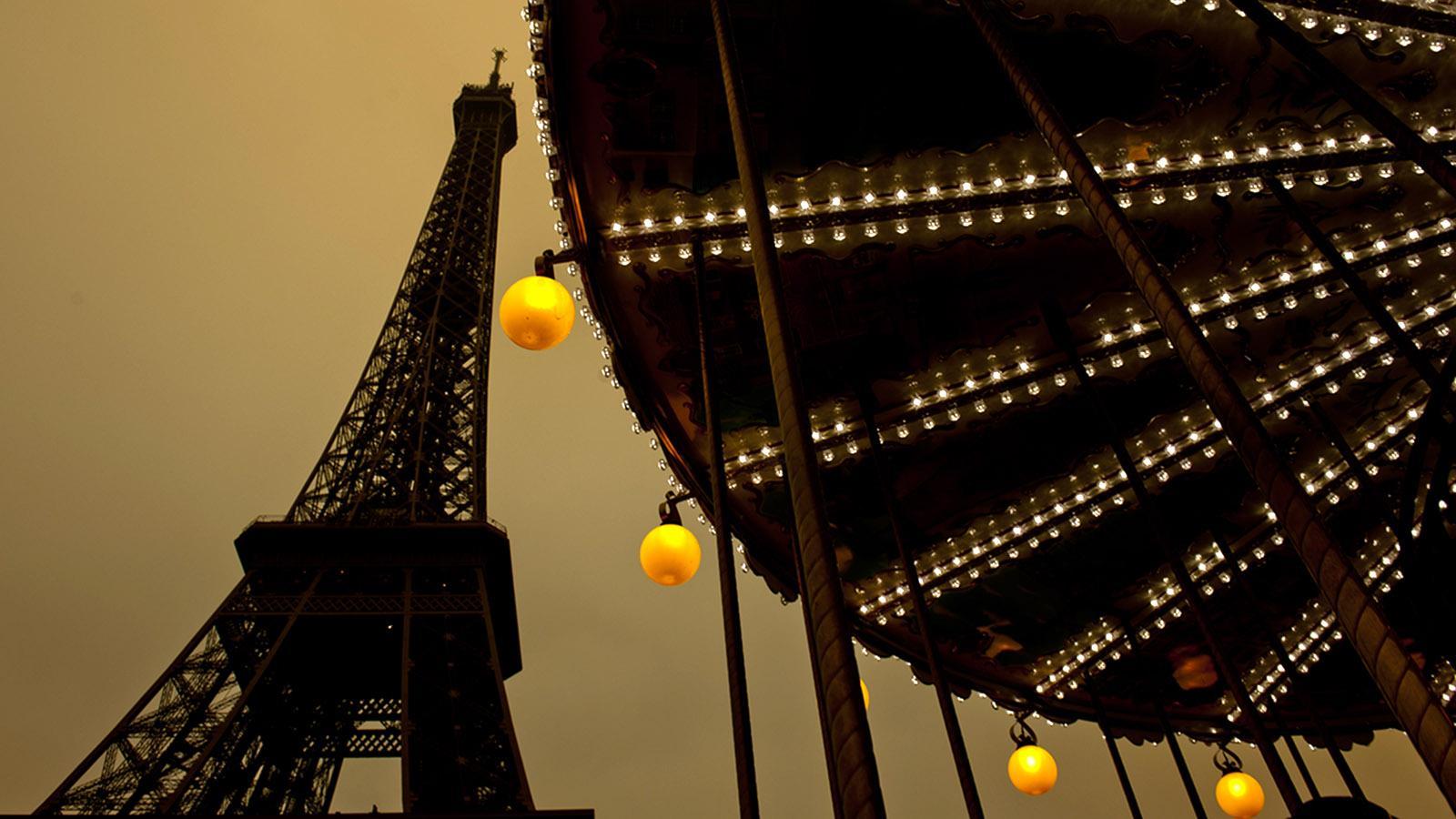 Der Eiffelturm (Tour Eiffel) am frühen Abend. Zu seinen Füßen dreht ein Karussell seine Runden. Foto: Hilke Maunder