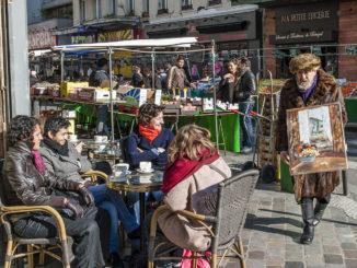 Märkte: An der Place d'Aligre preist ein Maler seine Kunst den Café-Gästen an. Foto: Hilke Maunder