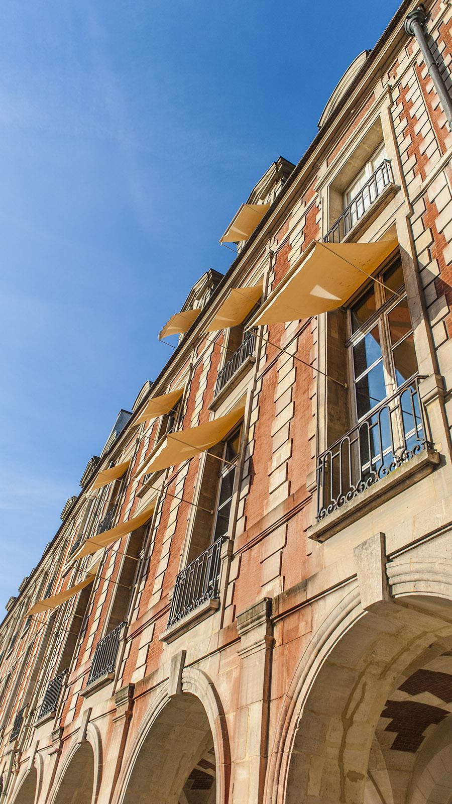 Stylisch in Textil: der Sonnenschutz auf den Fassaden der Place des Vosges. Foto: Hilke Maunder