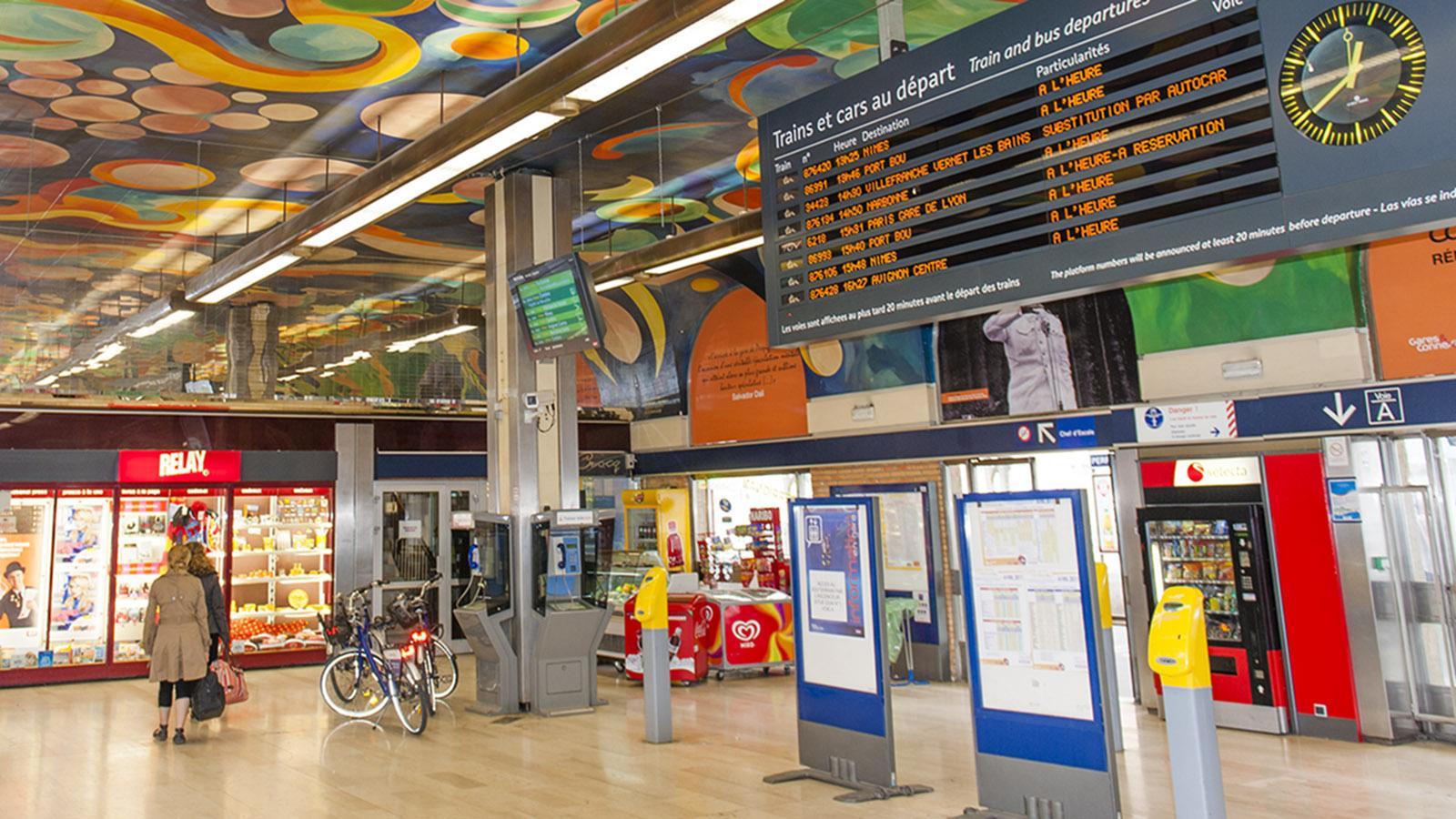 Bahnfahren in Frankreich. Der Bahnhof von Perpignan war bis vor wenigen Jahren kunterbunt im Innern - eine Hommage an DalI. Foto: Hilke Maunder