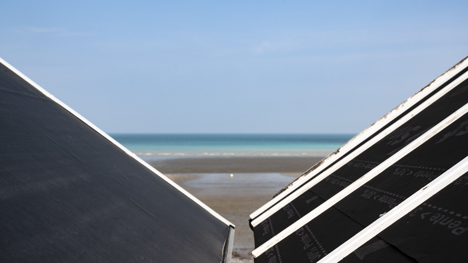 Blick durch die Strandhütten von Saint-Aubin aufs Meer. Foto: Hilke Maunder