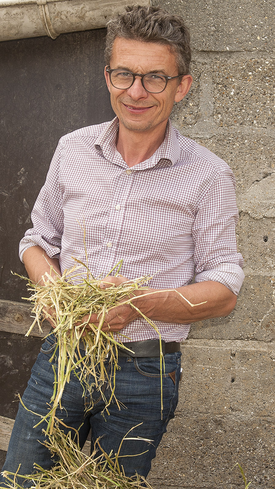 Boeuf Cidré: François-Xavier Craquelin mit dem Heu, das er verfüttert. Foto: Hilke Maunder