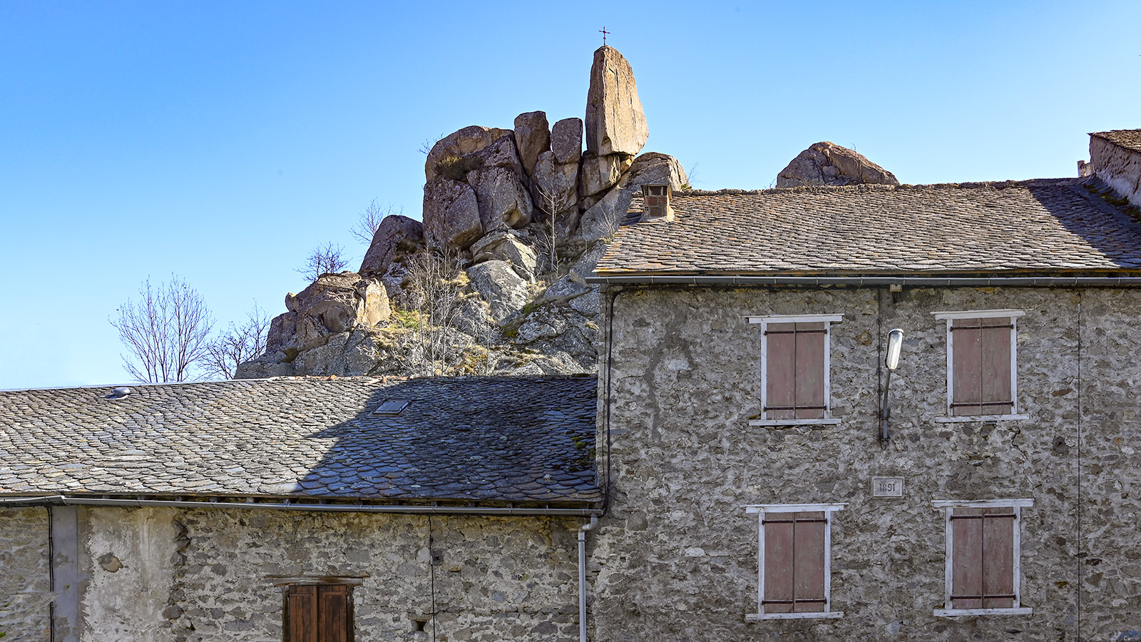 Von diesem Kreuz aus könnt ihr das Château de Quérigut vor den Bergspitzen der Pyrenäen. Foto: Hilke Maunder