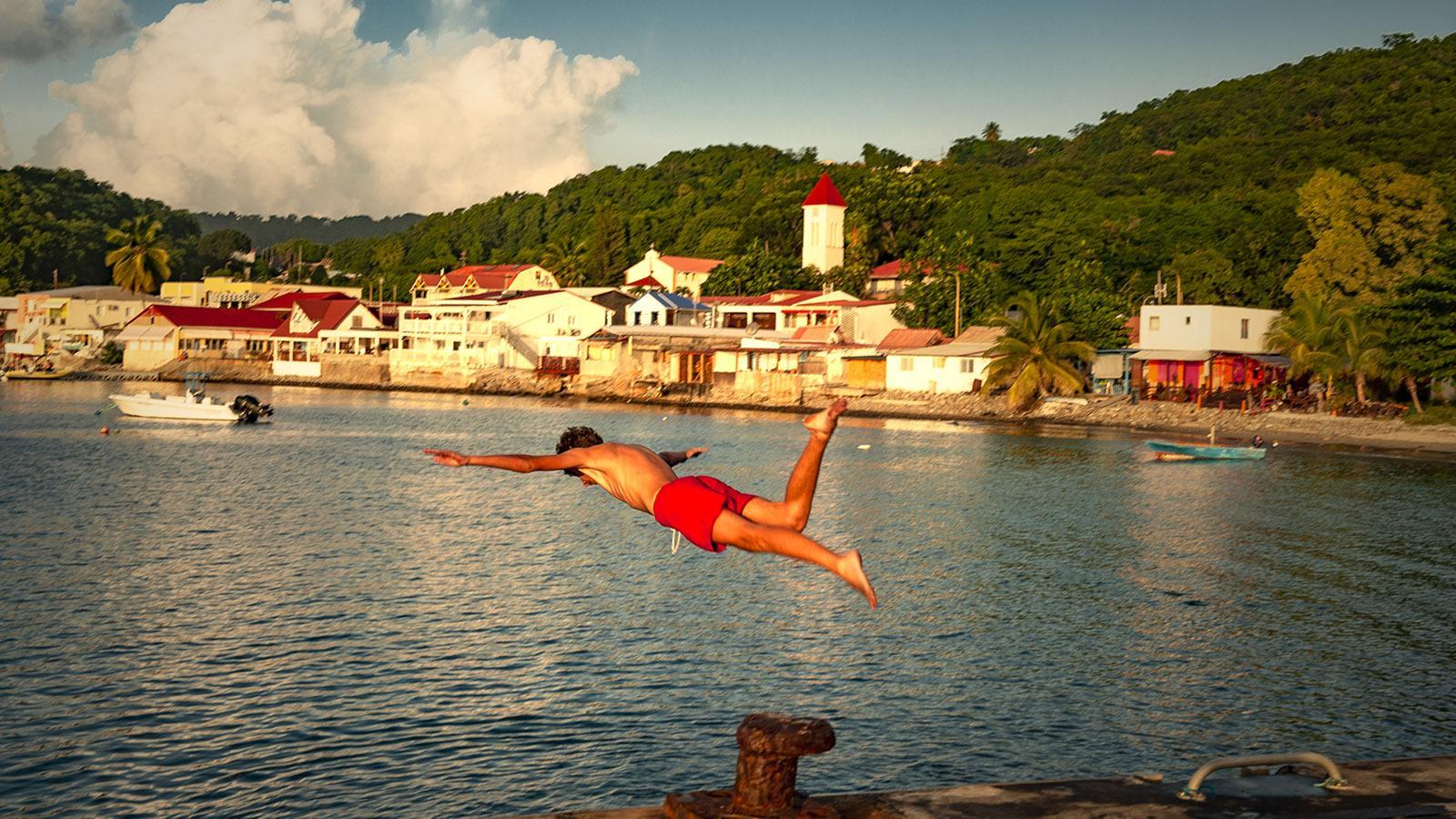 Guadeloupe: Von der Pier springen die einheimischen Jungs in die Bucht - auch Salti versuchen sie. Foto: Hilke Maunder