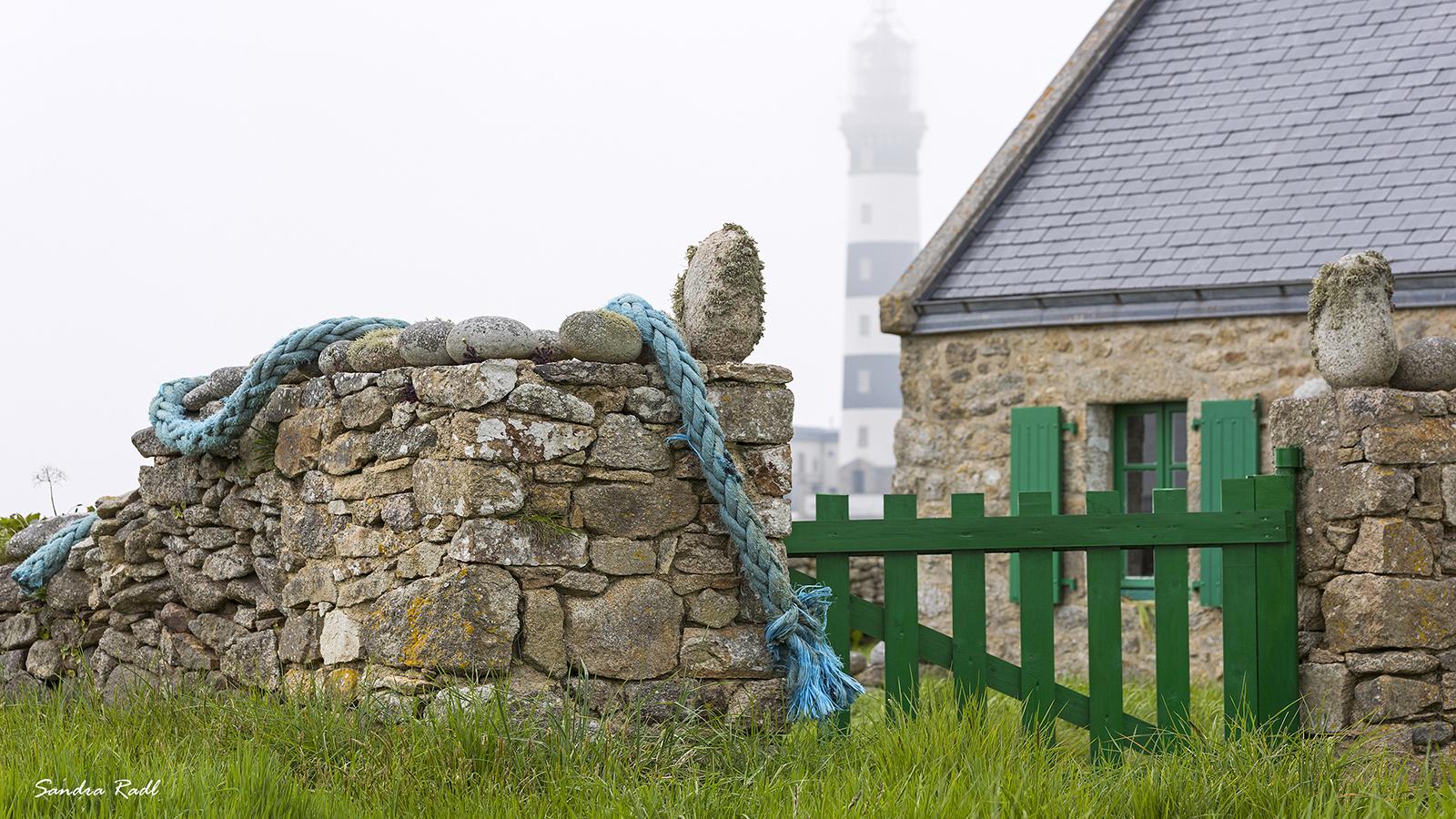 Steinhaus mit Steinmauer, durch den Nebel fällt der Blick auf den Phare du Créac'h. Foto: Sandra Radl