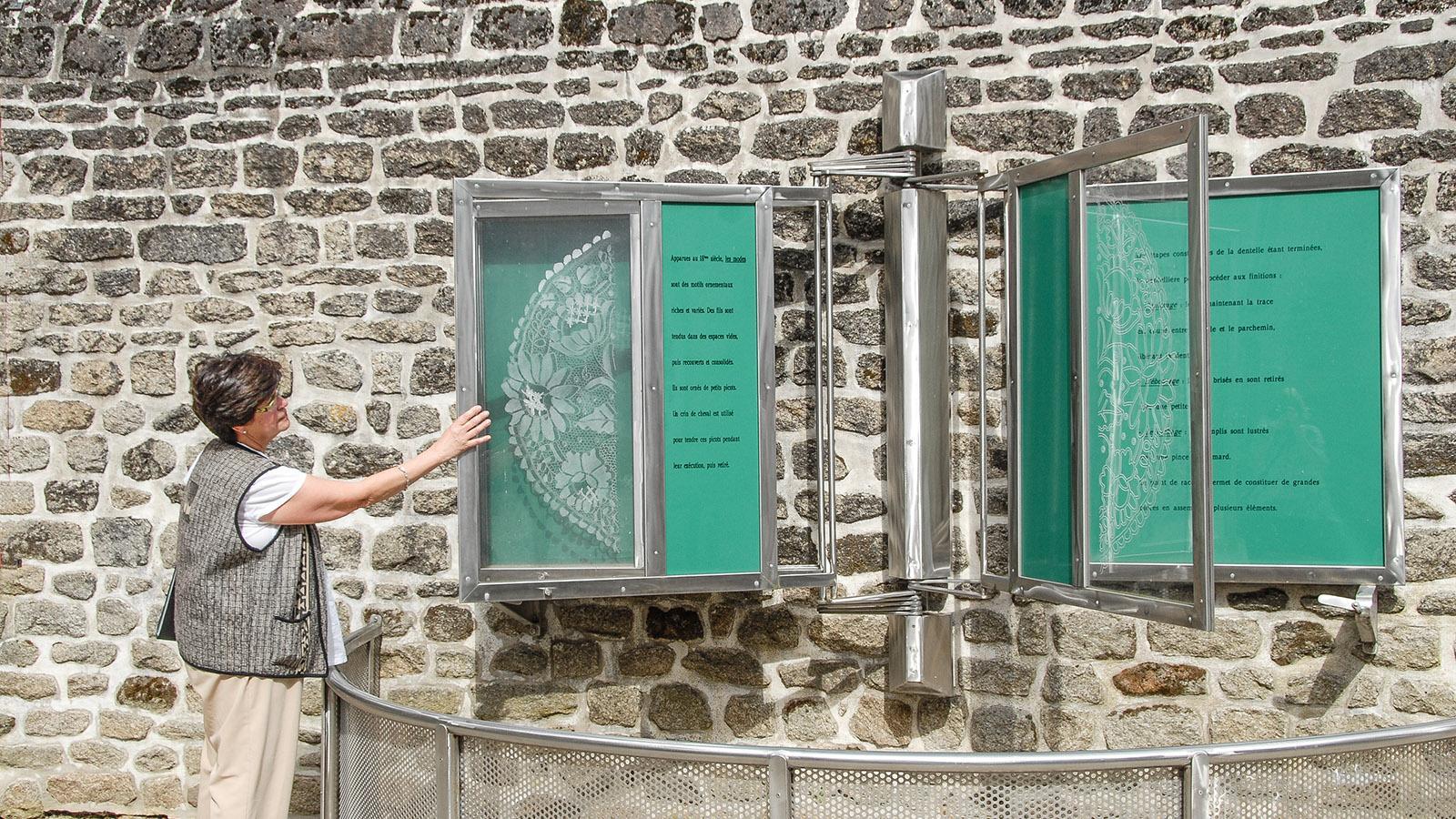 FVor der Fassade des Musée des Beaux Arts et de la Dentelle stellen Tafeln die Alençon-Spitze vor. Marie-Hélène Augé zeigt sie. Foto: Hilke Maunder