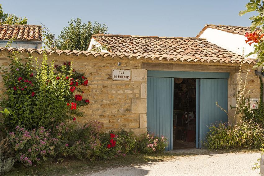 Naturstein, blaues Tor und Stockrosen: Talmont-sur-Gironde bleibt sich treu. Foto: Hilke Maunder